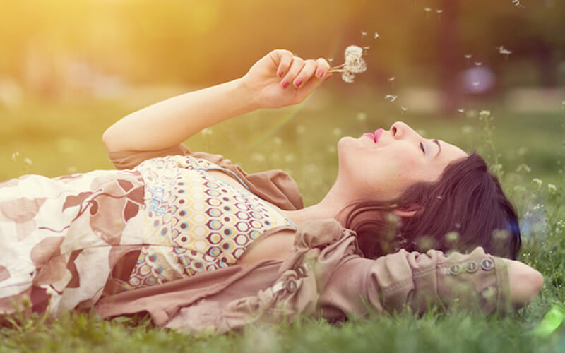 happy woman lying on the grass blowing on seedlings.
