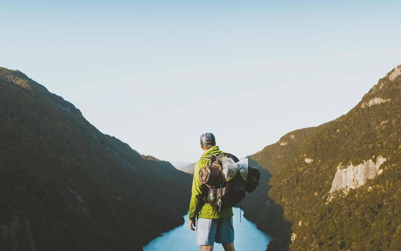 Man with backpack looking at a valley.